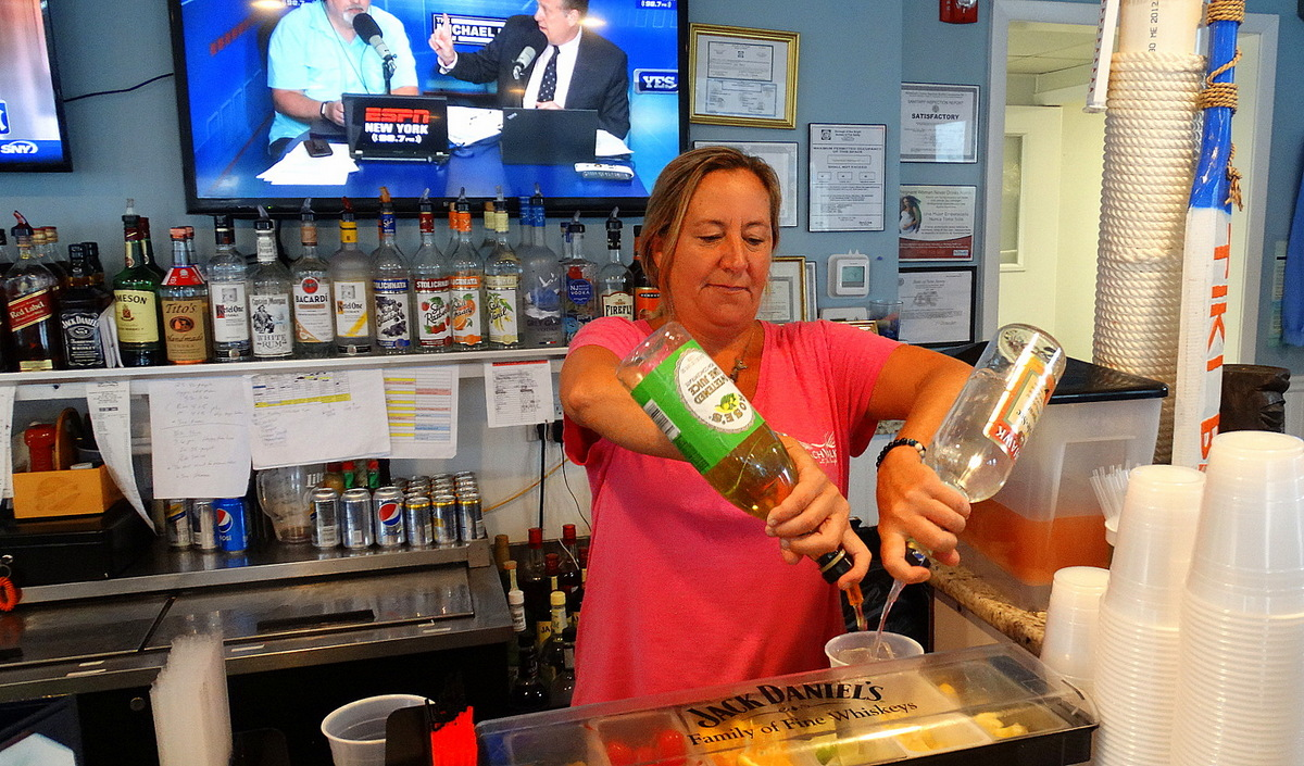 Bartender Erin O Keefe Makes A Long Island Ice Tea While Customers Some Still In Beach Garb Make Themselves Comfortable On The Deck Over River